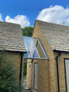Bespoke roof between customers home and outbuilding to keep owner sheltered